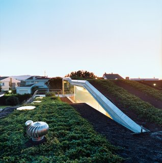 The hydroponic rooftop garden grows out of volcanic stones. The home is conceived as a giant C-shaped spiral.