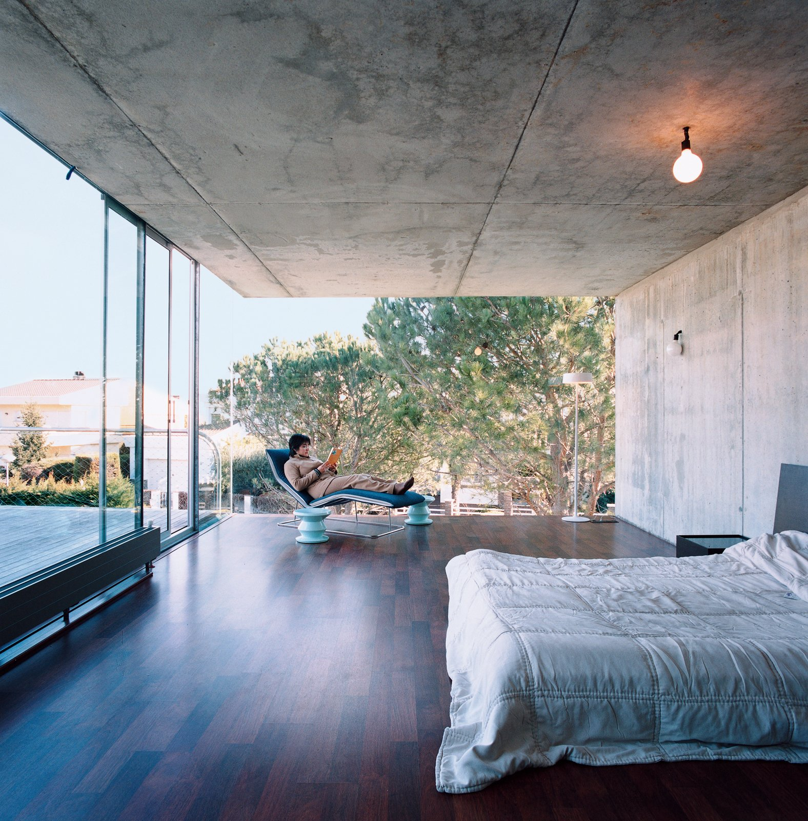 Giovanna de Uzin Fontecha relaxes in the master bedroom on a Leaf chaise by Claesson-Koivisto-Rune for Living Divani. Tagged: Bedroom, Bed, Chair, Ceiling Lighting, and Dark Hardwood Floor.  Striking Exposed Concrete Interiors by William Harrison from Suburban House of the Future by Cloud9