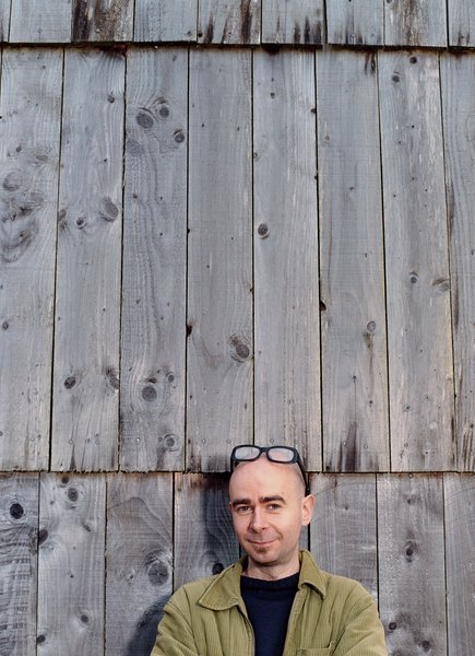 Architect Dominic Stevens in front of his timber-clad house in northwest Ireland.