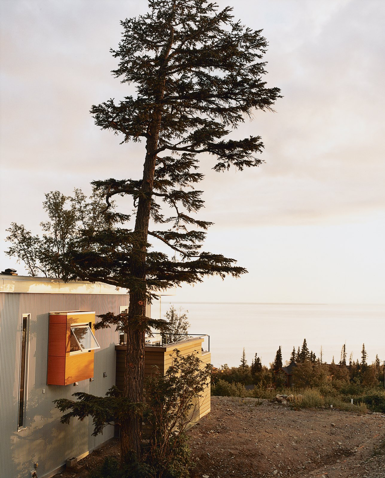Laid out in a 270-degree panorama in front of the house is the frosty expanse of Cook Inlet, cascading rocky mountains, and a white sun as big as a dinner plate. Tagged: Side Yard, Trees, Exterior, Metal Siding Material, House, and Metal Roof Material.  Photo 1 of 9 in Alaska: The Final (Architectural) Frontier