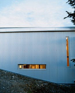 "Sattler-Smith explains that ""the north side of the house is covered with corrugated galvanized steel and pierced with only a few very small windows; this protects from the 100-mile-per-hour north winds."""