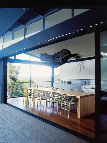 Caroline Casey designed the curving dining table, which is surrounded by Hans Wegner's Wishbone chairs. Suspended over the table is an old Aboriginal fishing trap.
