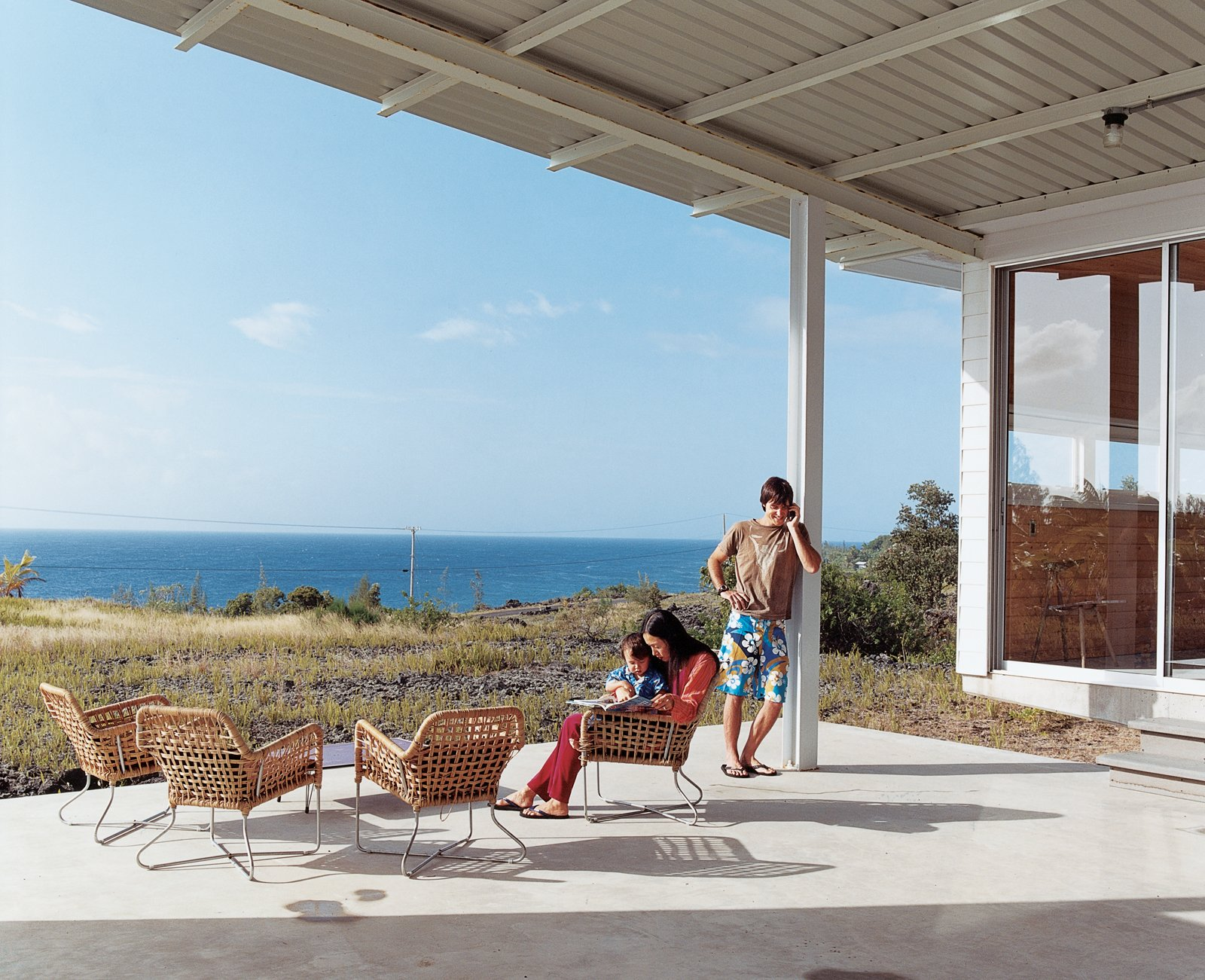Architect Craig Steely designed this house for himself, his wife Cathy Liu, a painter, and their son, Zane, that looks out to the Pacific Ocean from a lava flow on the big island of Hawaii. Tagged: Outdoor, Large Patio, Porch, Deck, and Concrete Patio, Porch, Deck.  Photo 1 of 11 in Go With the Flow