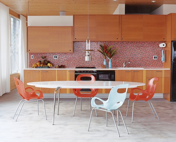 The concrete floor takes on a silky appearance in the kitchen and dining areas. The Gideå table is from IKEA, the Karim Rashid Oh chairs are from Umbra, and the Erik Magnussen kerosene Ship's lamp is by Stelton.