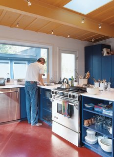 "Primary colors and uncomplicated spaces define the interiors of both sheds. Golob is shown above in the modest open kitchen, where appliances were chosen for ""cost, durability, and efficiency."""