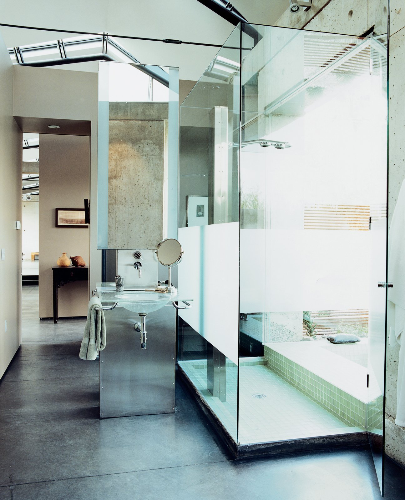 The dramatic bathroom features a glass sink designed and cast by Mies Grybaitis of OIA. The etched glass shower is accented by green glass tile. Tagged: Bath Room, Enclosed Shower, and Concrete Floor.  Photo 11 of 11 in Love's Labors Found