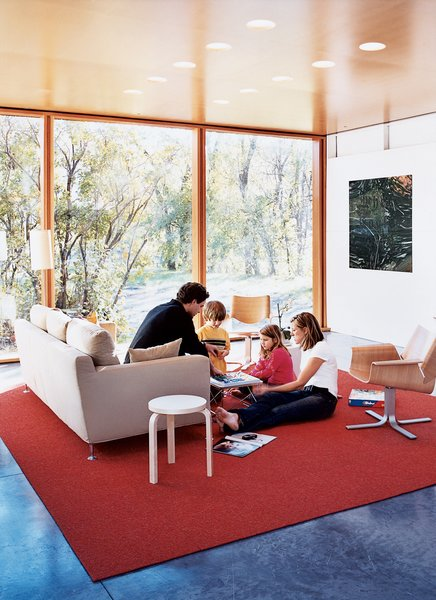 "Having lived, he says, in ""a number of houses where the living room is the most adorned and the least used,"" it was important for Lazor to create a functional family living space. As the gathering above attests, it worked. The carpet is by InterfaceFLOR, and the armchairs by Blu Dot."