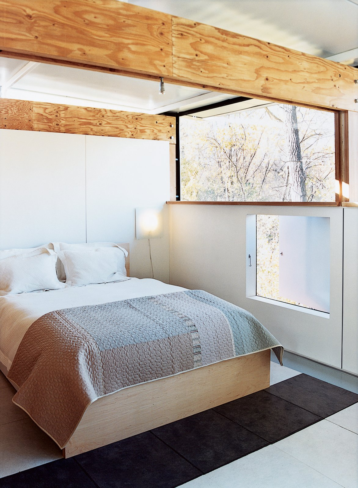 The master bedroom features a low-level picture window that opens out to the green space behind the house.  Prefab by Dan Perjar from How to Play FlatPak