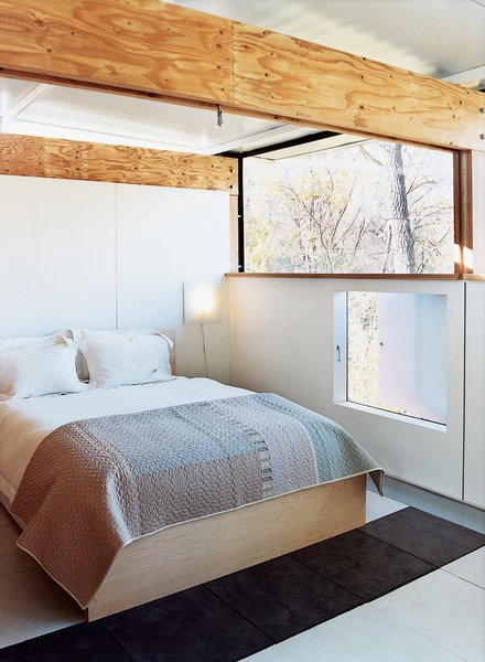 The master bedroom features a low-level picture window that opens out to the green space behind the house.