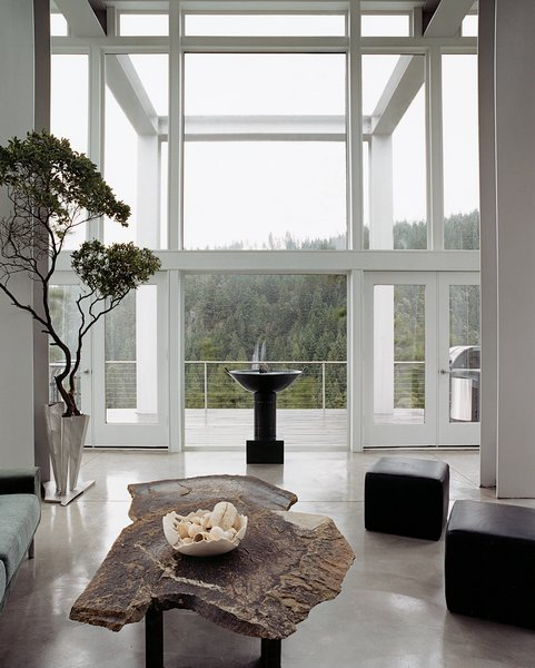 The living room looks out toward the two waterfalls that are also part of the property and the inspiration for its name. Artist Constantin Hapaianu made the coffee table and the stainless steel railings surrounding the staircase.