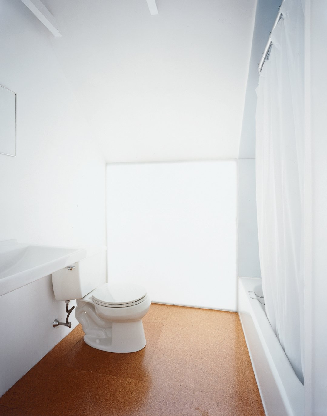 Upstairs, simple porcelain pieces such as a Kohler toilet adorn the modest master   bathroom. Beneath the downward-pitched ceiling, a polycarbonate-panel wall brings in light from the south-facing skylight behind.
