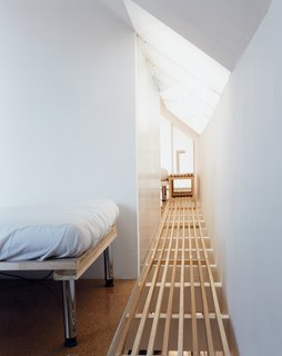 An ingenious floor treatment—slats laid over the ceiling beams—enables the skylight to do double duty, pouring sunlight into the living room below. The translucent bathroom wall turns that into triple duty.