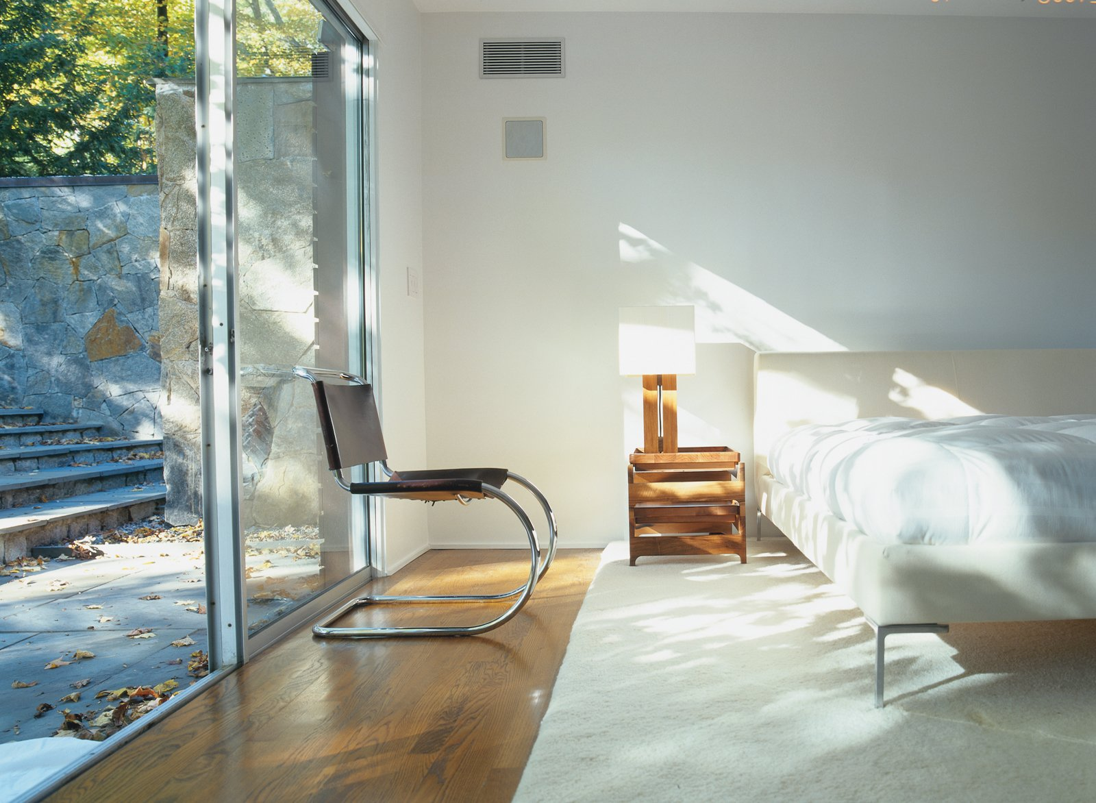 The master suite was fashioned from the house's original garage in a 1970s renovation. Tagged: Bedroom, Bed, Chair, and Medium Hardwood Floor.  Photo 6 of 6 in Pursuing Perfection