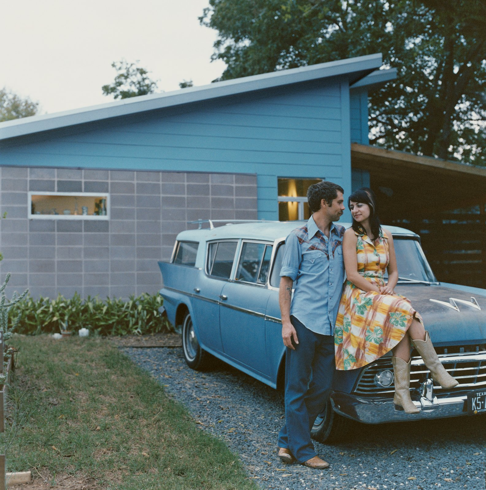 Andy and Regina Rihn lean on their other blue-clad affordable design, a 1958 AMC Rambler Super station wagon, in front of their house in Austin, Texas. Tagged: Exterior and House.  Best Western: Our Favorite Modern Homes in Texas by Aaron Britt from A Lot for a Little