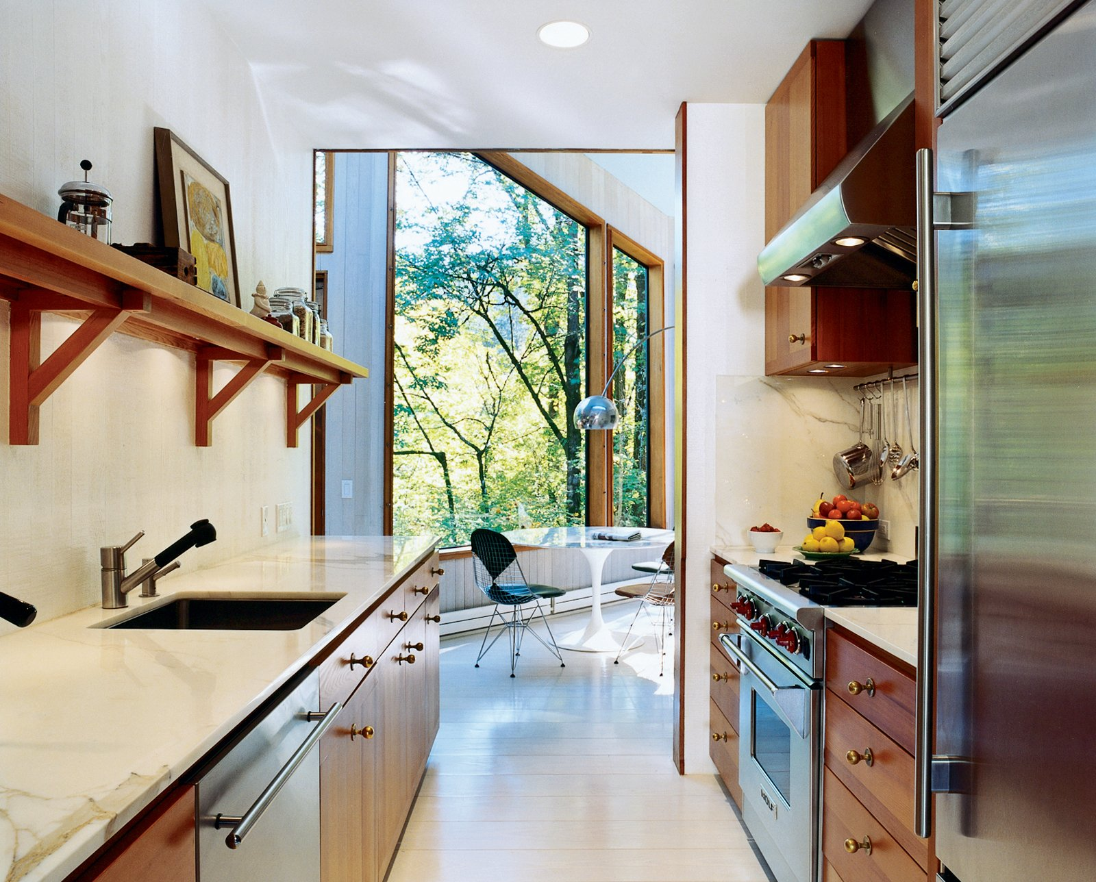 To brighten the kitchen, which was once the darkest room, Watson and Tschopp decided on a glossy white finish, painted directly on the same rough-cut cedar paneling used throughout the house. This maintains the consistency of materials and texture, while reflecting light and enhancing the natural illumination. Stainless steel appliances and vintage bronze hardware add luster. Super White semigloss (walls) and Old Pick Up Blue (ceilings) are by Benjamin Moore. Tagged: Kitchen, Marble Counter, Refrigerator, Range, and Marble Backsplashe.  Photo 3 of 6 in The Pace of Portland