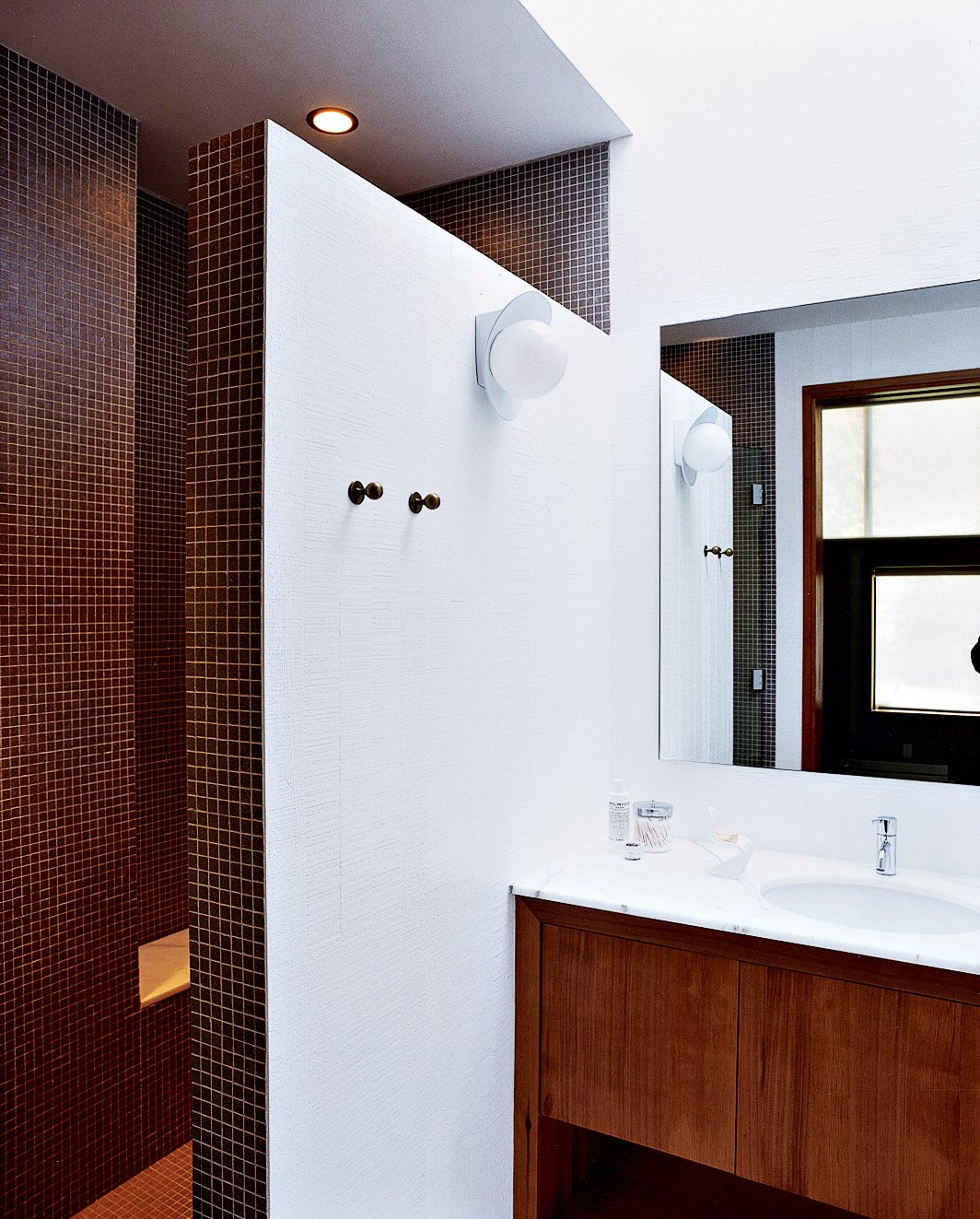 A double-size shower, clad floor-to-ceiling in tiny earth-toned tiles, was built after relocating the water heater and claiming its space. A chic yet discreet toilet is wall-hung and the tank concealed, greatly ameliorating the somewhat claustrophobic feel of the original bathroom. Tagged: Bath Room, Marble Counter, Enclosed Shower, Full Shower, Ceiling Lighting, and Ceramic Tile Wall.  Photo 5 of 6 in The Pace of Portland