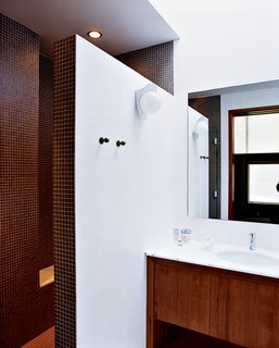 The Pace of Portland - Photo 5 of 6 - A double-size shower, clad floor-to-ceiling in tiny earth-toned tiles, was built after relocating the water heater and claiming its space. A chic yet discreet toilet is wall-hung and the tank concealed, greatly ameliorating the somewhat claustrophobic feel of the original bathroom.