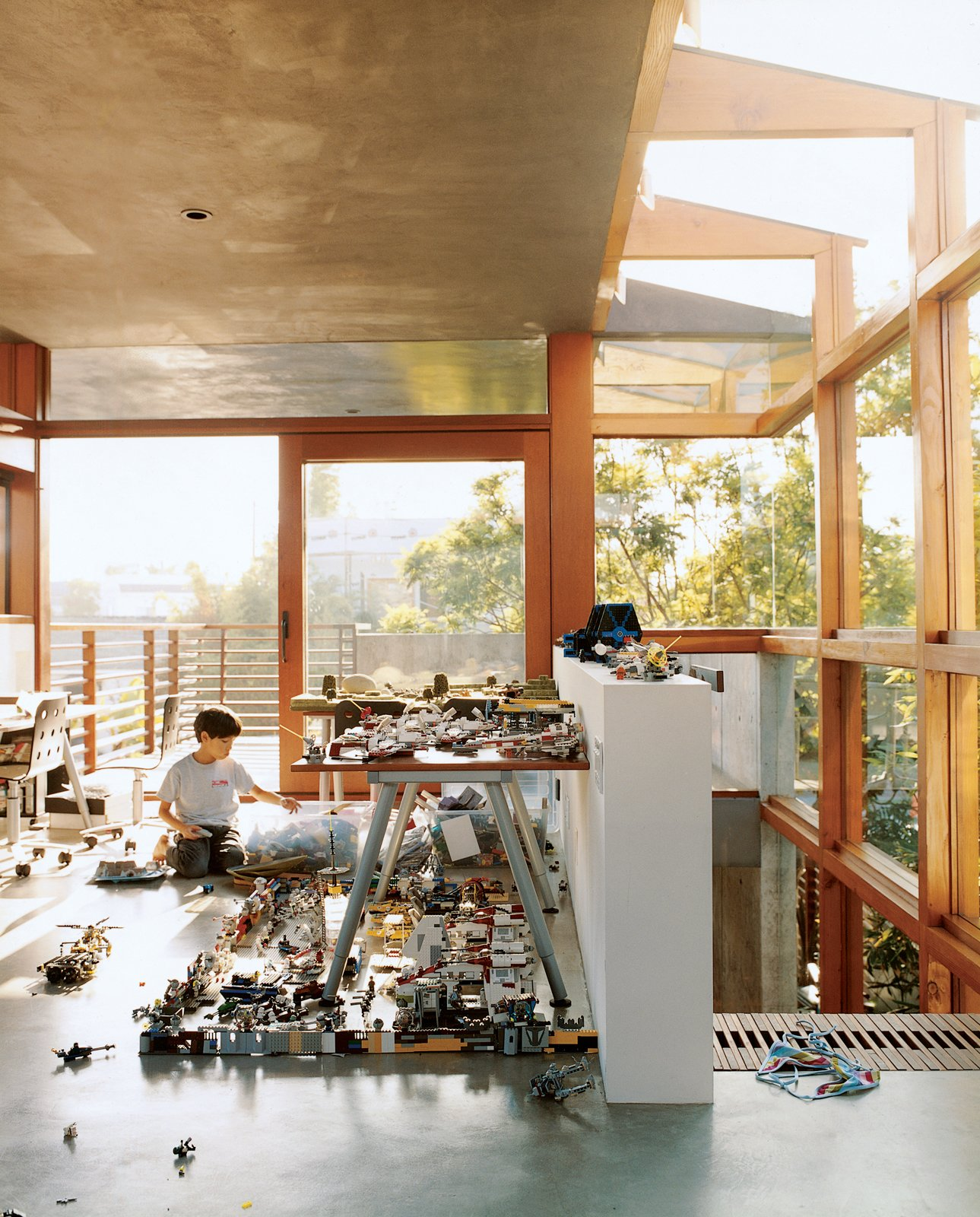 In the new addition to the Hertz/Fong residence, the architect's son Max tinkers with his extensive array of Legos and War Hammer miniatures in the upstairs office/playroom. Sustainability in Stages - Photo 1 of 6