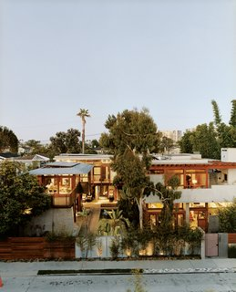The exuberant results of Hertz's design are visible from the street. Giant birds <br><br>of paradise, king palms, and bamboo tower above the fence. The Balinese long building, seen on the far left, is almost nautical; on the right, the original house's rammed-earth entry wall frames its concrete layers.