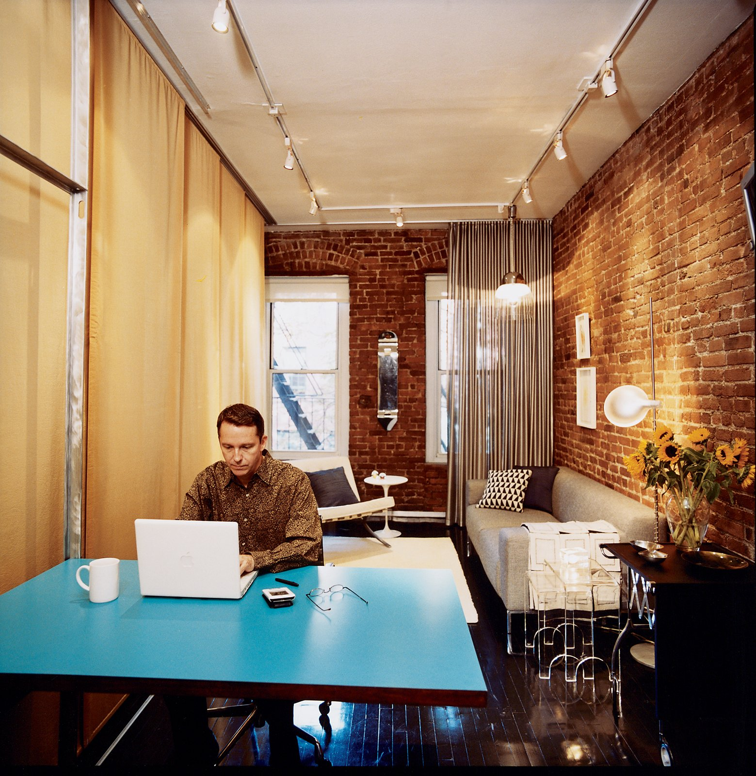 Checking email over coffee, Hughston places his laptop on the fold-down Formica table that Sanders designed. Jack Lenor Larsen's Cybelle fabric covers the wall on his right. Above the sofa hangs an Italian pendant lamp of mysterious origin; if you recognize it, please contact us. Tagged: Living Room and Dark Hardwood Floor.  Photo 2 of 6 in A 400-sq-ft New York Apartment Gets a Second Chance