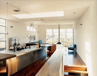 A long, narrow rectangle functions as a kitchen, dining, working, and general gathering area. Skylights set at a 90-degree angle to the workstation boost the dynamism in the room and cast a bright glow over the unit's walnut-and-steel seam.