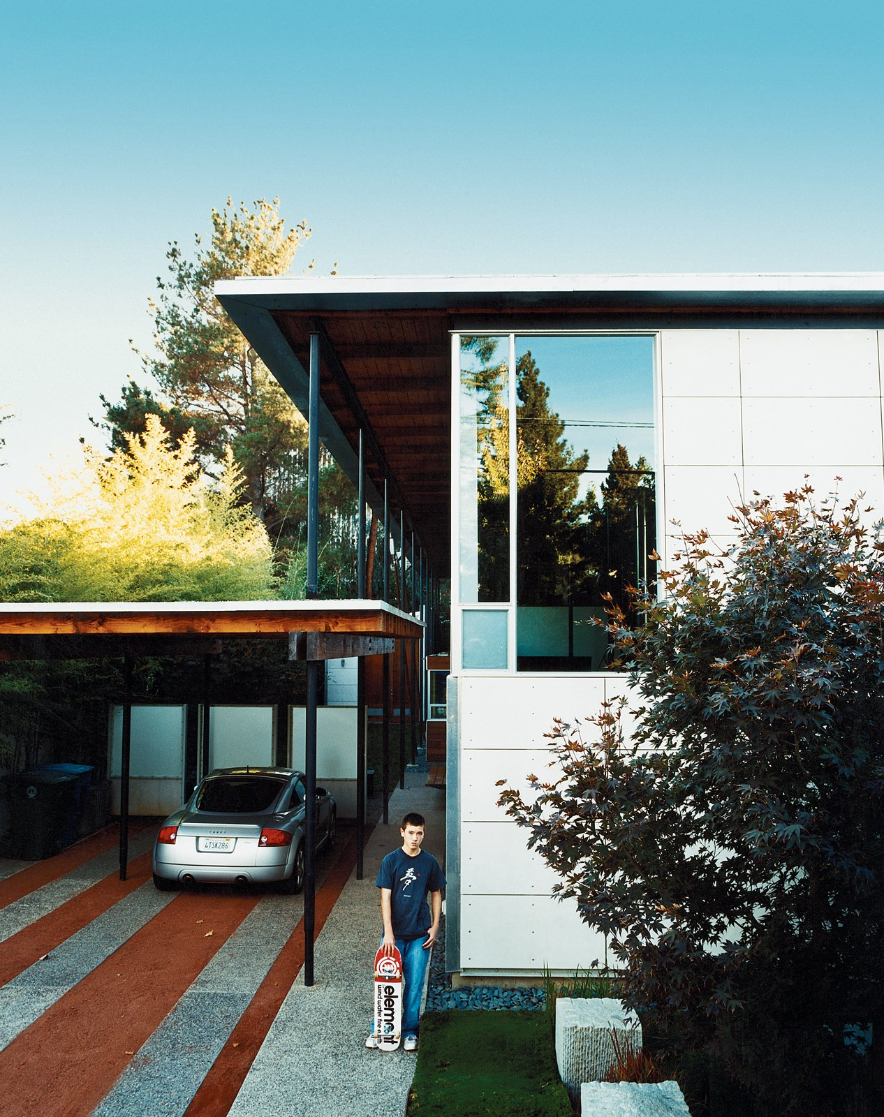 Turning its back to the street and next-door apartment like a curled-up cat, the long, narrow house spills out sideways to the garden, designed by landscape architect Andrea Cochran.  Bold Suburban Homes by William Harrison from The New Suburbanism