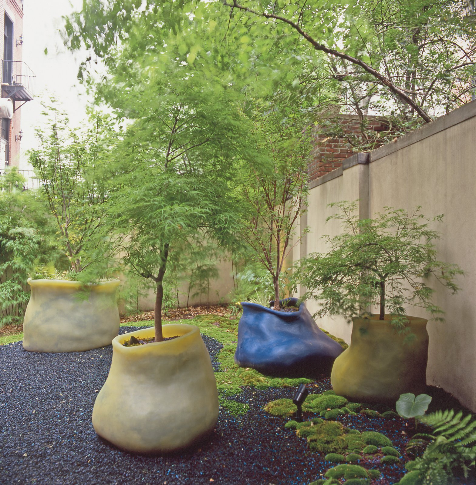 A cluster of maple trees sprout from a trio of Autumn Lake eccentric silicone planters and a Ginko medium classic planter in the courtyard of Hayes' gallery, Salon 94.