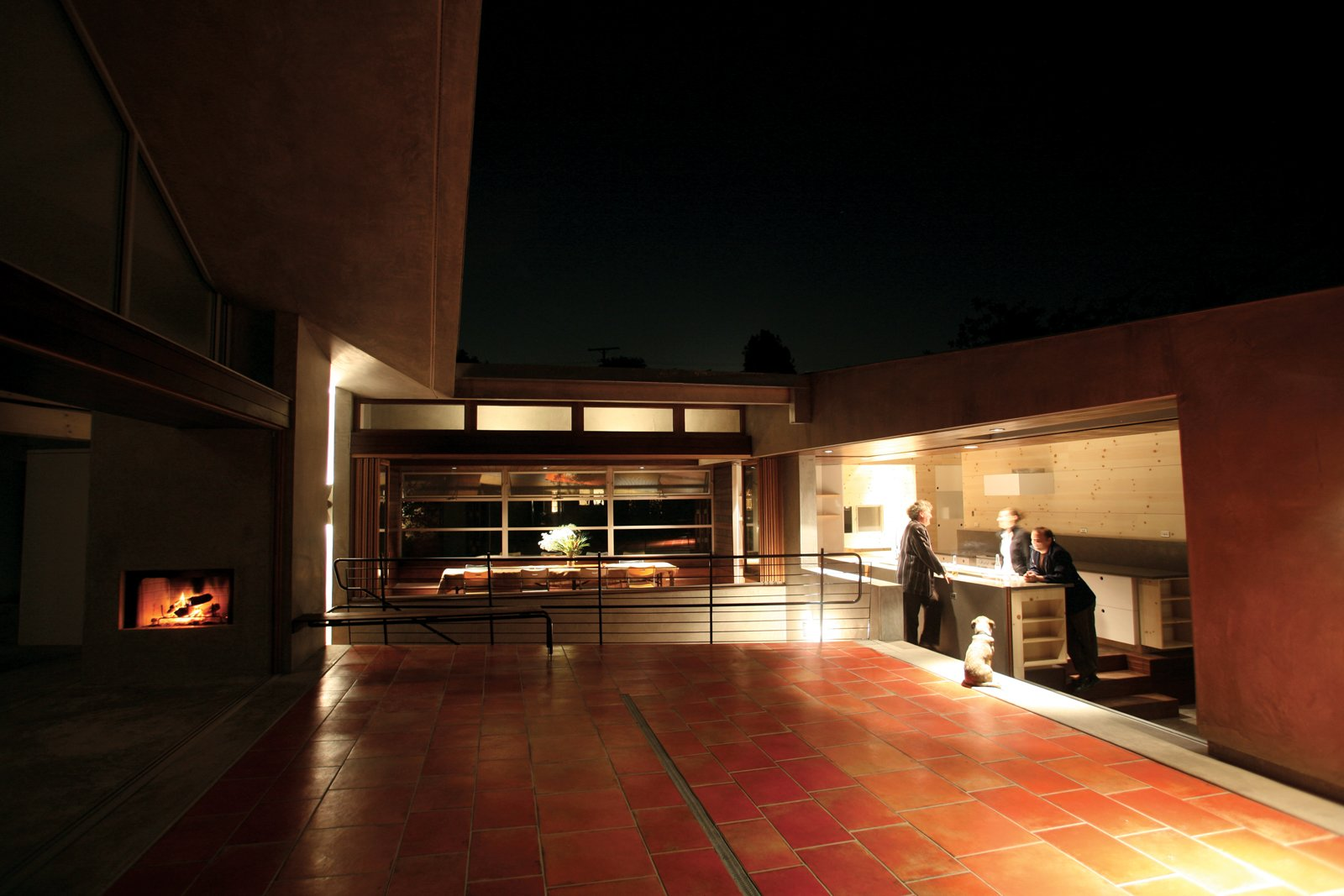 """The two sides of the house look across the courtyard at each other, and are bridged by the dining room, which looks out onto the street below like the wheelhouse of a ship. """"Everyone ends up in the kitchen anyway, so why not put the kitchen in the courtyard?"""" says Robertson. The kitchen features a NanaWall system that opens directly to the outdoors. The only two enclosed rooms in the house are the bedrooms.  Courtyard House by David A. Greene"""