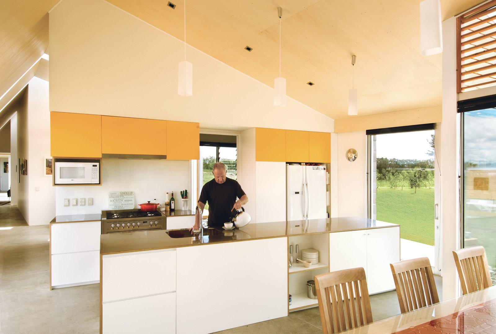 Ted Preston takes charge of hot beverages in the kitchen. The architects diligently avoided cold, hard minimalism with a honey-tinged Italian poplar ceiling.