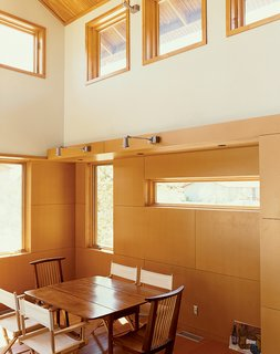 8 Bright and Airy Wood-Paneled Spaces - Photo 1 of 8 - With smooth, clear-finish MDF tile-like panels that accentuate carefully located joints, this living/dining area feels bright and modern, especially thanks to the double-height ceilings and multiple windows that let in natural light. Light pours into the Ankneys' living/dining area with its clear pine plywood ceiling, clear-finish MDF paneling on the walls, and reclaimed-fir flooring.