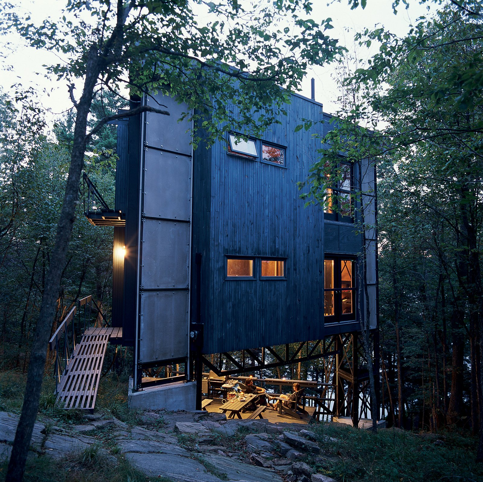 Scrap steel and reclaimed wood clad the three-story triangular tower, which hovers over a small deck and outdoor space.