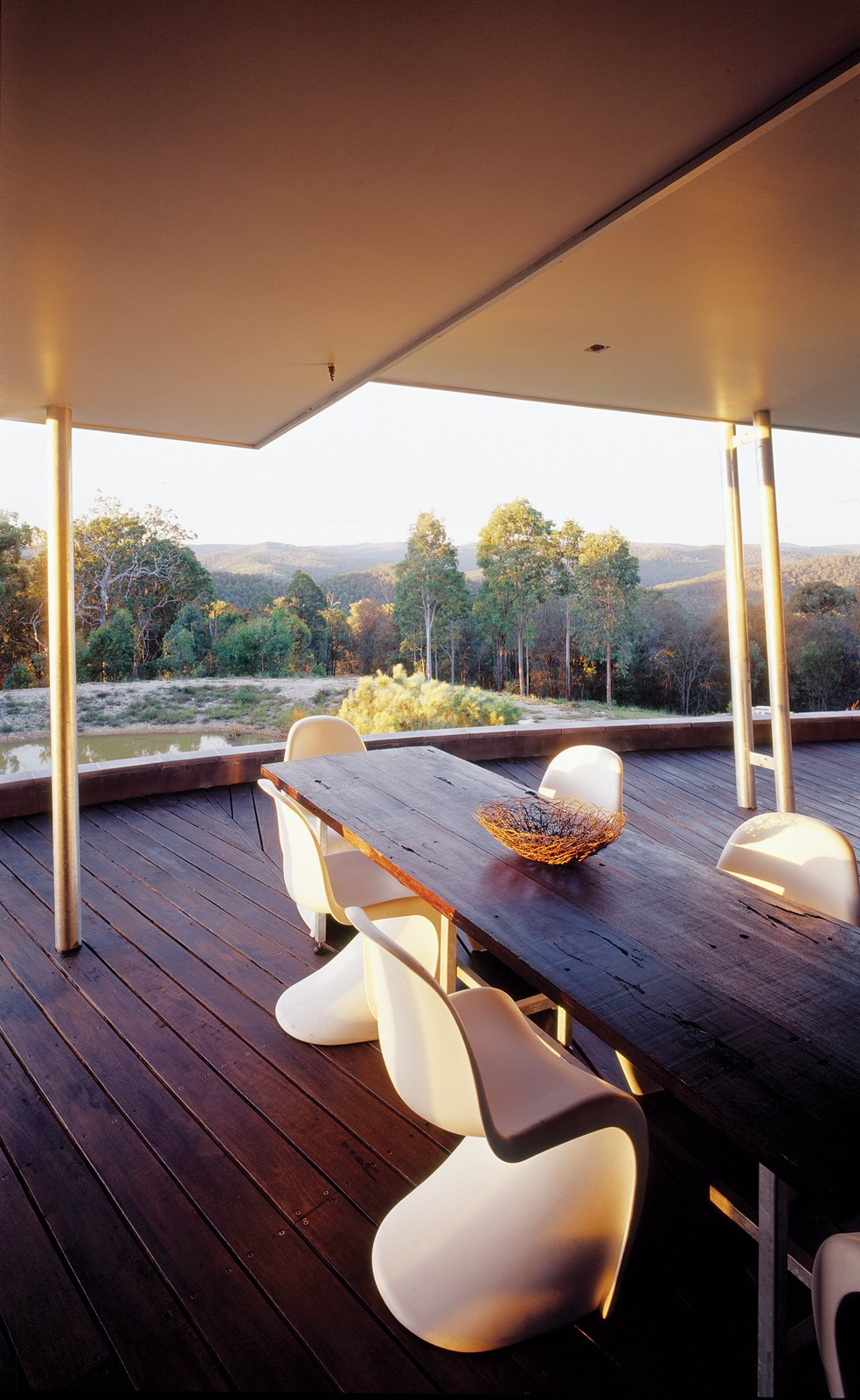 """Outside, the family can enjoy an unspoiled view of their massive """"backyard"""" from their reclaimed wood table, surrounded by Panton chairs.  Photo 5 of 5 in Winds of Change"""