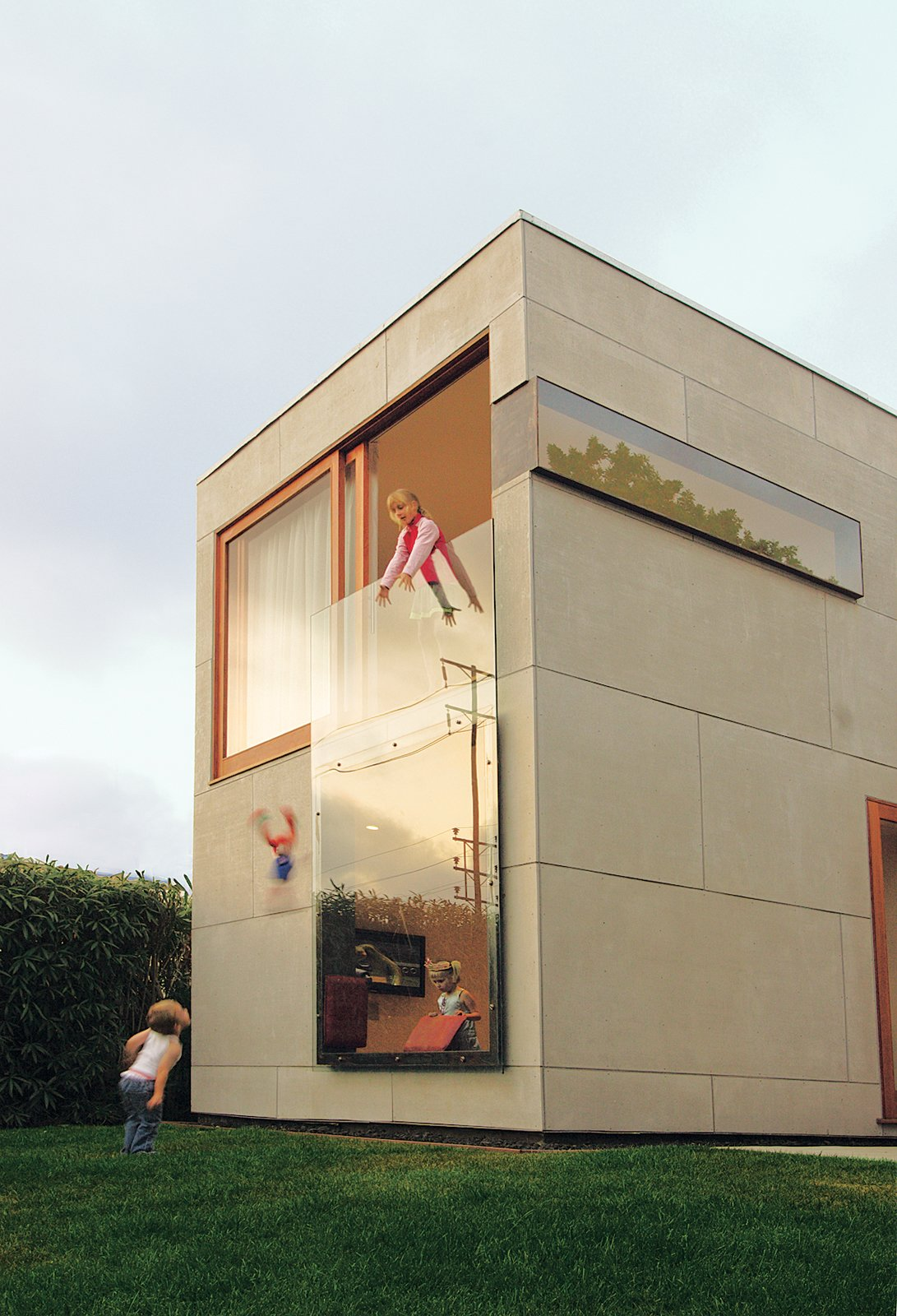An 8-by-12-foot piece of tempered glass on the front of the house serves as a window for the first-floor den and a railing for the second-floor office. Tagged: Outdoor and Grass. Building Green in Santa Monica - Photo 3 of 5