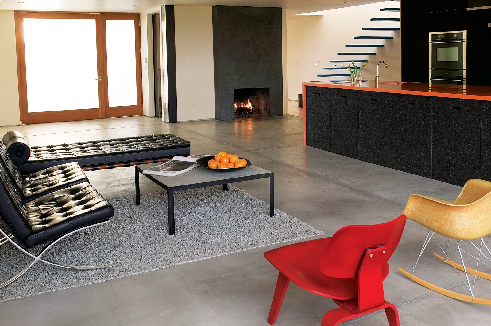 The sides of the orange Corian kitchen counter are clad in recycled rubber. Tagged: Living Room, Chair, Recessed Lighting, Sofa, Wood Burning Fireplace, Concrete Floor, Rug Floor, and Coffee Tables.  Photo 5 of 5 in Building Green in Santa Monica