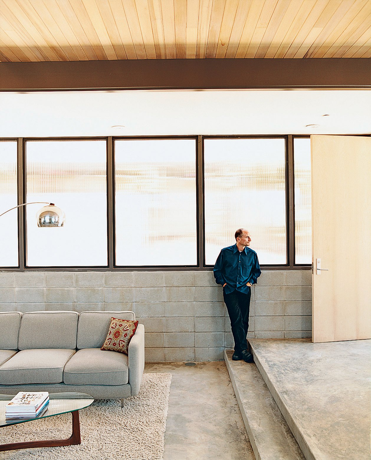 Glenn looks toward the front entrance from the northeast wall of his house. The wall is exposed concrete block with translucent Polygal windows. Tagged: Living Room, Sectional, and Concrete Floor.  Photo 3 of 7 in LEEDing the Way