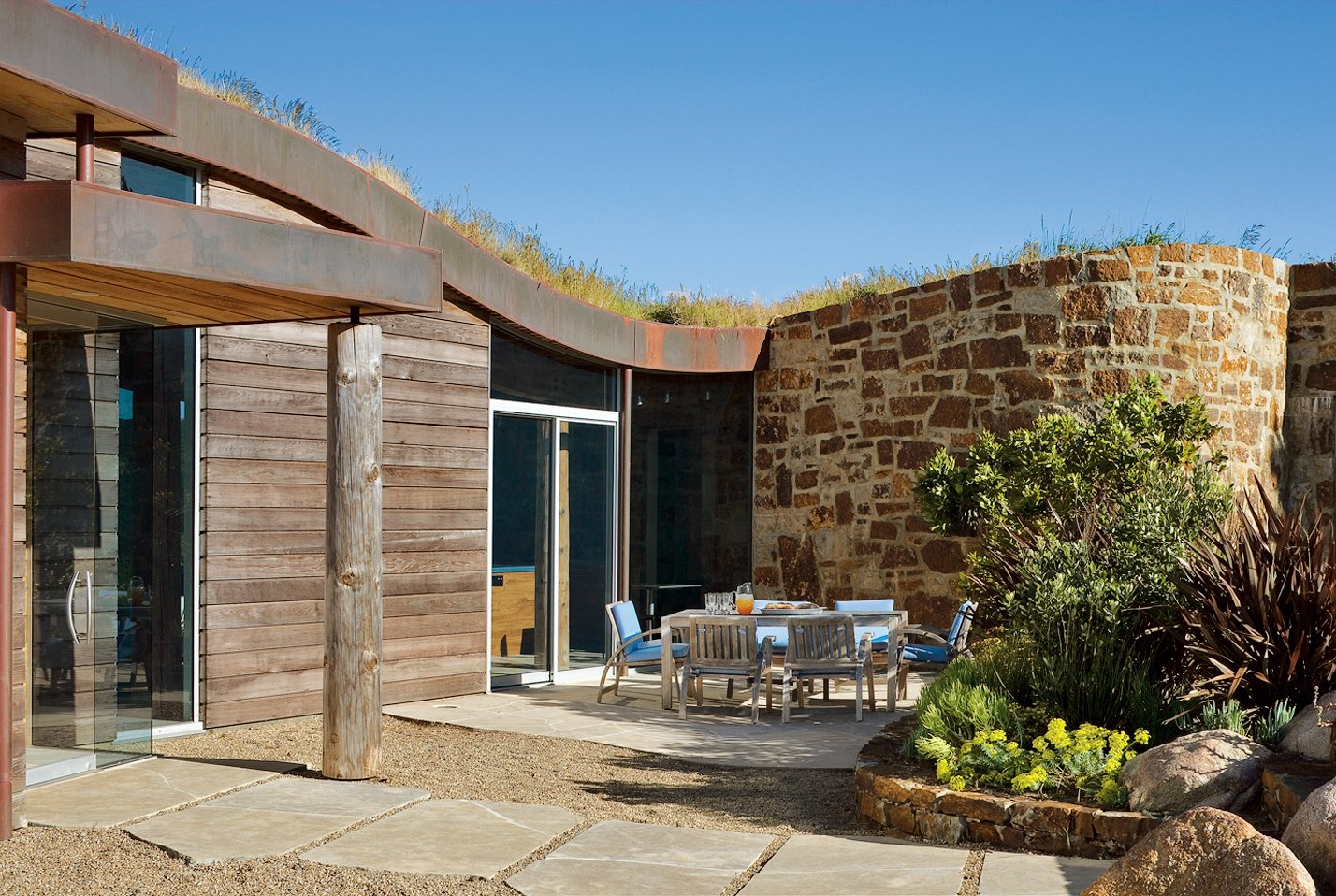 The structure sits lightly on a stone patio that cuts into the hillside site.