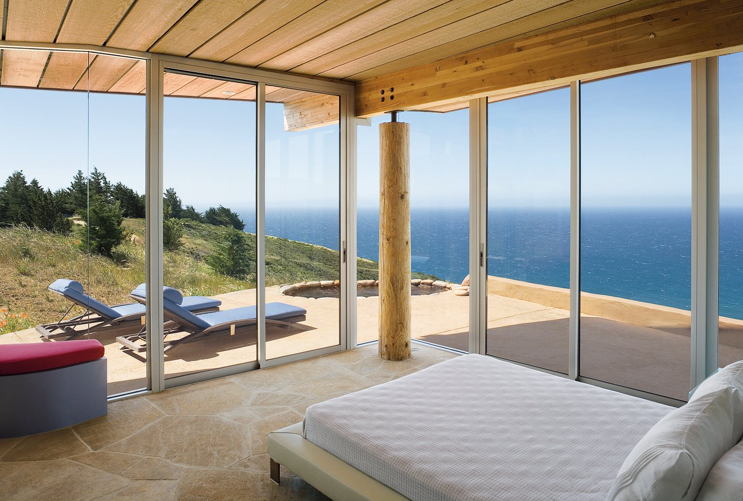 Two walls of floor-to-ceiling windows in the master bedroom frame expansive vistas of the Pacific Ocean. Tagged: Bedroom and Bed. Big Sur: Going Coastal - Photo 4 of 6