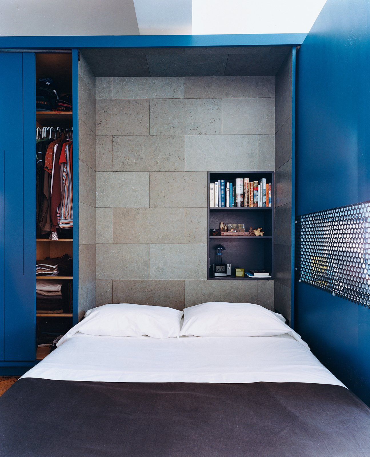 The interior of the Murphy bed compartment is lined with a stained cork panel and contains a smaller shelving unit for bedside reading, alarm clock, and reading lamp.  Bedrooms by Dwell from You Can Do It All in 450 Square Feet