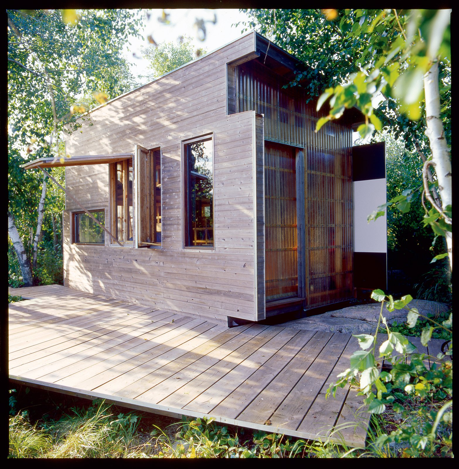 The exterior is clad in an elegant mish-mash of cedar, plywood, glass, and fiberglass panels. Tagged: Exterior and Wood Siding Material.  Photo 3 of 5 in Barely There
