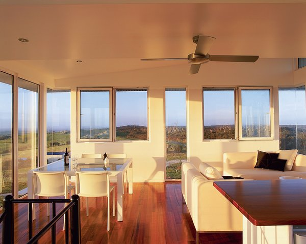 Walls of windows in the kitchen and living area frame uninterrupted views of a forest and the ocean.