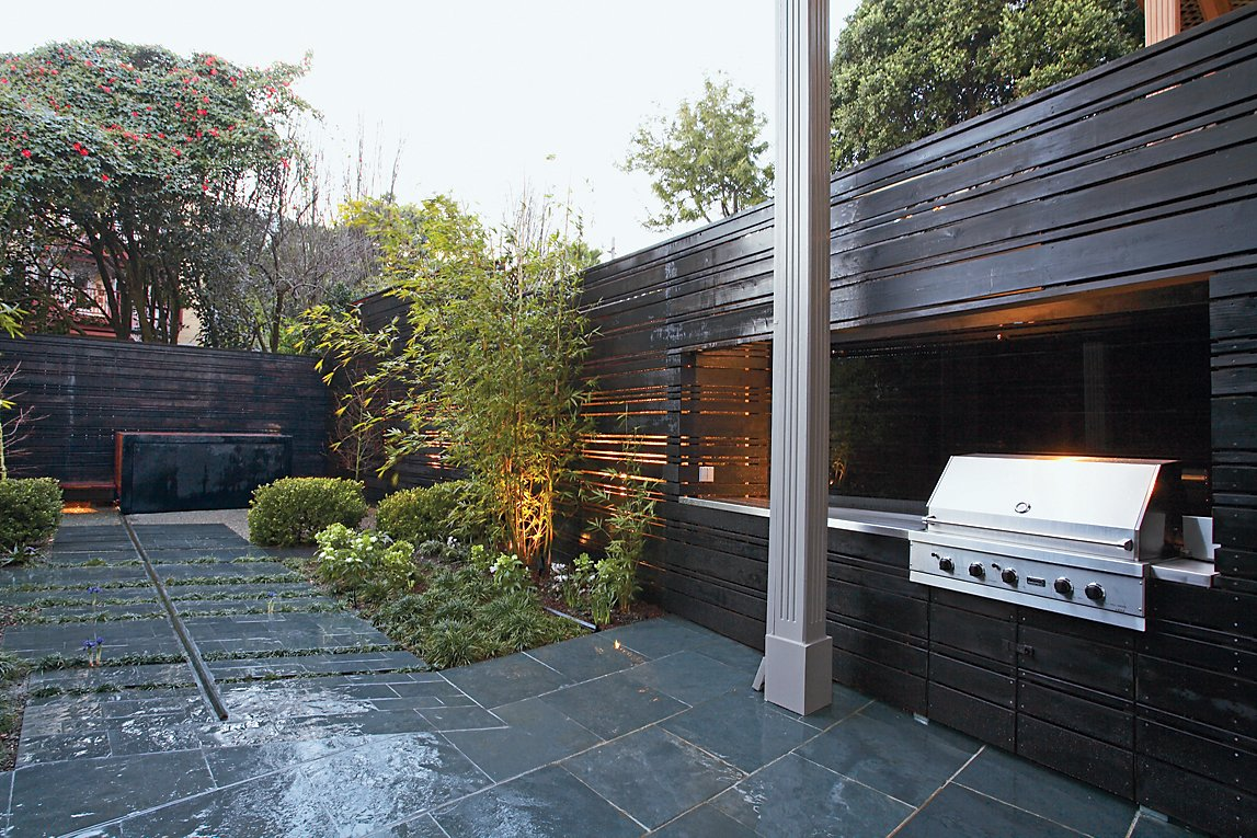 The landscape architects expanded an existing stone patio to include a bamboo grove, a boxwood hedge, and the ipe-and-steel hot tub.