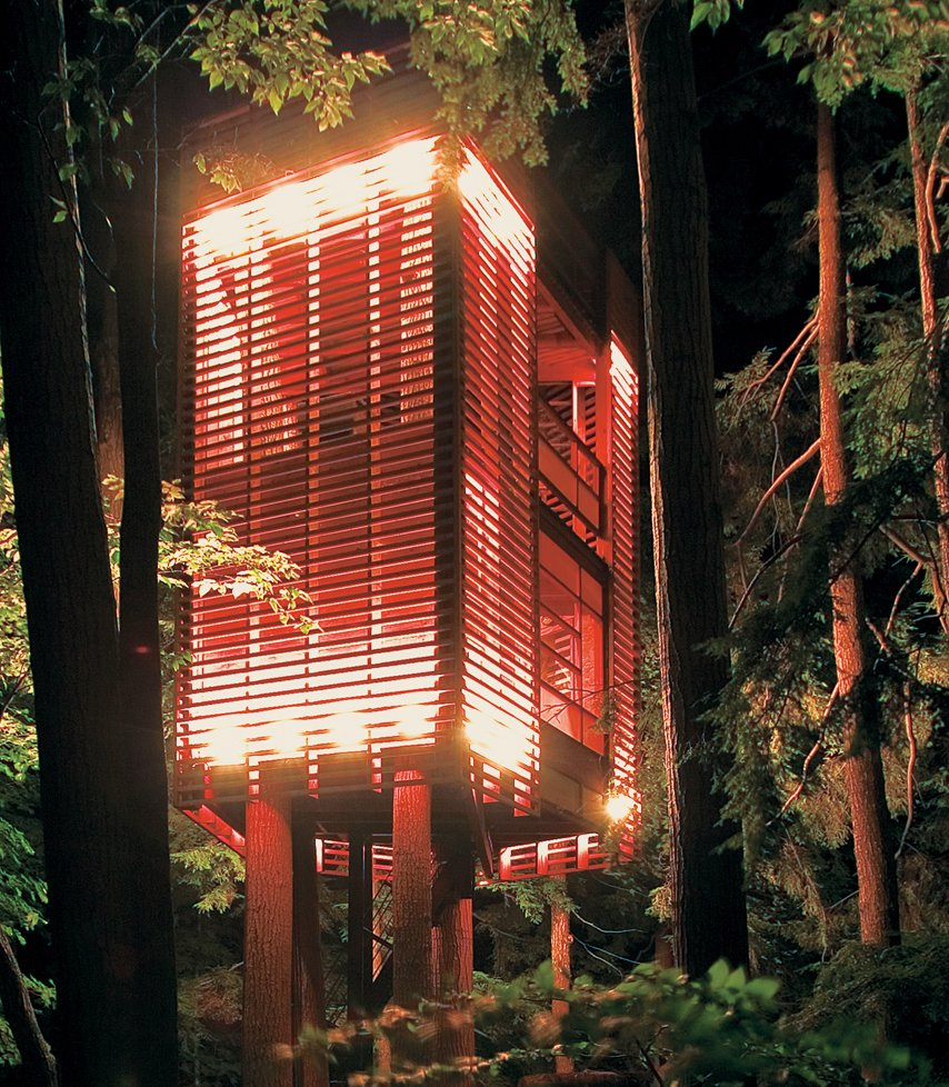 """This was really a parameter-driven project,"" explains Lukasz Kos, a Toronto-based designer and cofounder of the architecture firm Testroom. ""That is, I had to let the trees decide how the tree house would be.""  What the trees decided, apparently, was that they wanted a gracefully slender, Blade Runner–like elevator lodged between them. They also decided they didn't want to be too mutilated in the process. Kos responded to their needs with the low-impact 4Treehouse, a lattice-frame structure that levitates above the forest floor of Lake Muskoka, Ontario, under the spell of some witchy architectural magic.  He created this effect by suspending the two-ton, 410-square-foot tree house 20 feet above the ground with steel airline cables. With only one puncture hole in each of the four trunks into which the cable is anchored, the trees get away almost entirely unscathed, and the structure attains the visual effect of being suspended weightlessly in midair.   At the base of the tree, a staircase rolls on casters upon two stone slabs, allowing occupants to enter and exit regardless of how much the tree house may be swaying or rocking in the wind. Solid plywood walls punctuated by a floor of red   PVC constitute the ""opaque"" base story, which is largely protected from the outside elements. ""The idea was to have the tree house open up as it gained elevation,"" explains Kos. The second story is surrounded by a vertical lattice frame, allowing for breezes, air, and light to filter softly through walls while still establishing a visual perimeter between outside and inside space. At top, the tree house is completely penned in, a suspended patio with a ceiling of sky.  br> br>Photo by Lukasz Kos. Tagged: Exterior, Wood Siding Material, Cabin Building Type, Treehouse Building Type, Tiny Home Building Type, and Flat RoofLine.  Photo 91 of 101 in 101 Best Modern Cabins from Suspended Habitation"
