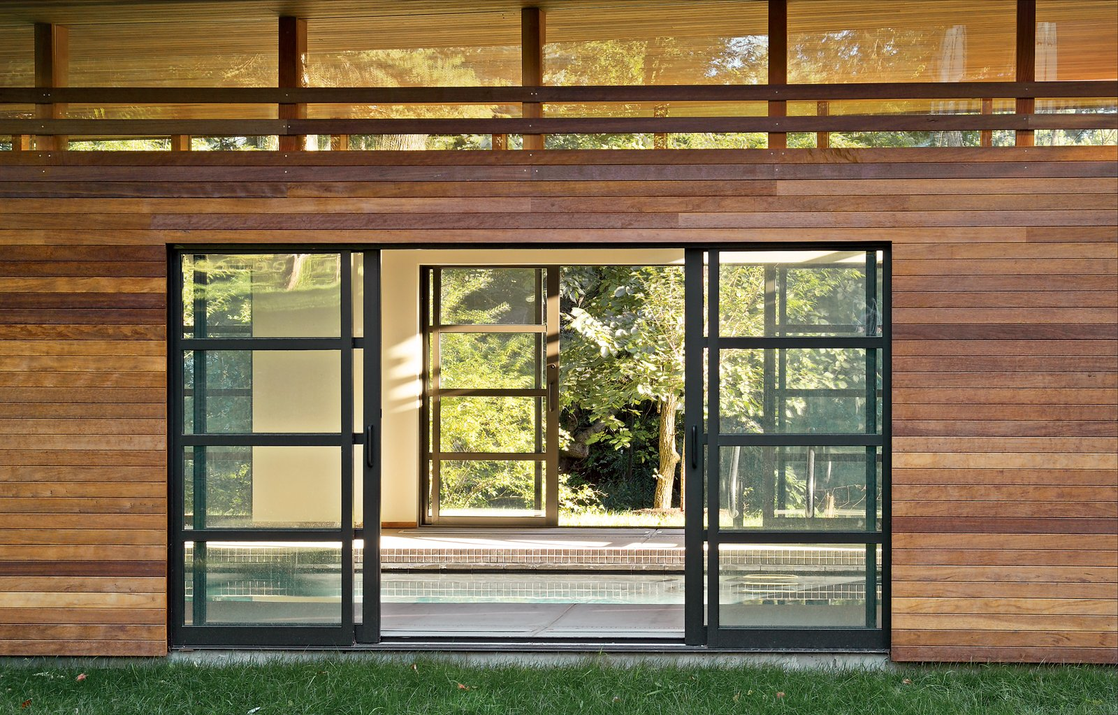 Sliding glass doors open to reveal the interior of the pool house, which boasts a line of clerestory windows just below the roof. Tagged: Doors.  Shining Examples of Clerestory Windows by Luke Hopping from Skinny Dip