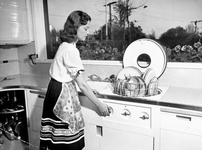 Mrs. Fritz Burns in her dream kitchen, using her built-in hydraulic dishwasher, in a Los Angeles house designed and built in 1946 in by her contractor husband, Bob Landry.  Photo 4 of 5 in Yesterday's Kitchen of Tomorrow