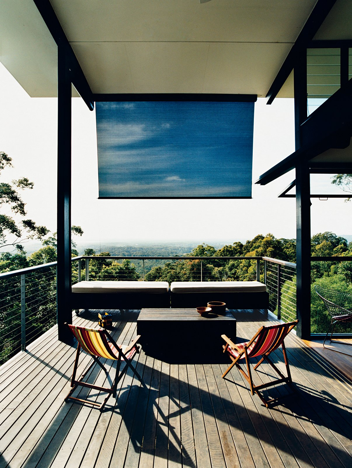 A large deck off the living room overlooks the hills of Noosa and the Pacific Ocean. Tagged: Outdoor, Small Patio, Porch, Deck, and Wood Patio, Porch, Deck.  Photo 2 of 12 in Hillside Family Home in Australia