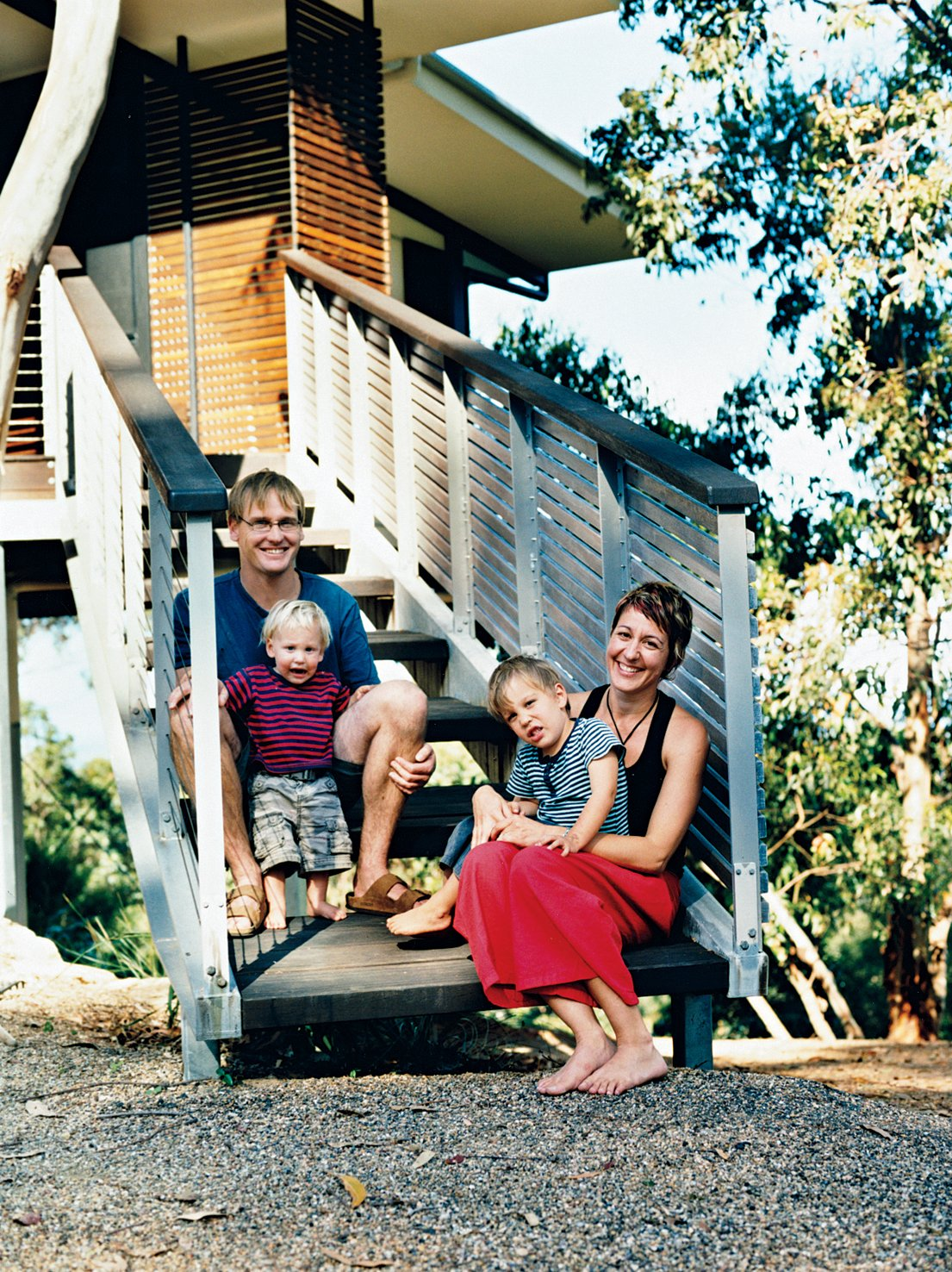 Stefan Dunlop and Adrienne Webb repose on their front entrance stairs with their sons Keanu and Kobe.  Photo 3 of 12 in Hillside Family Home in Australia