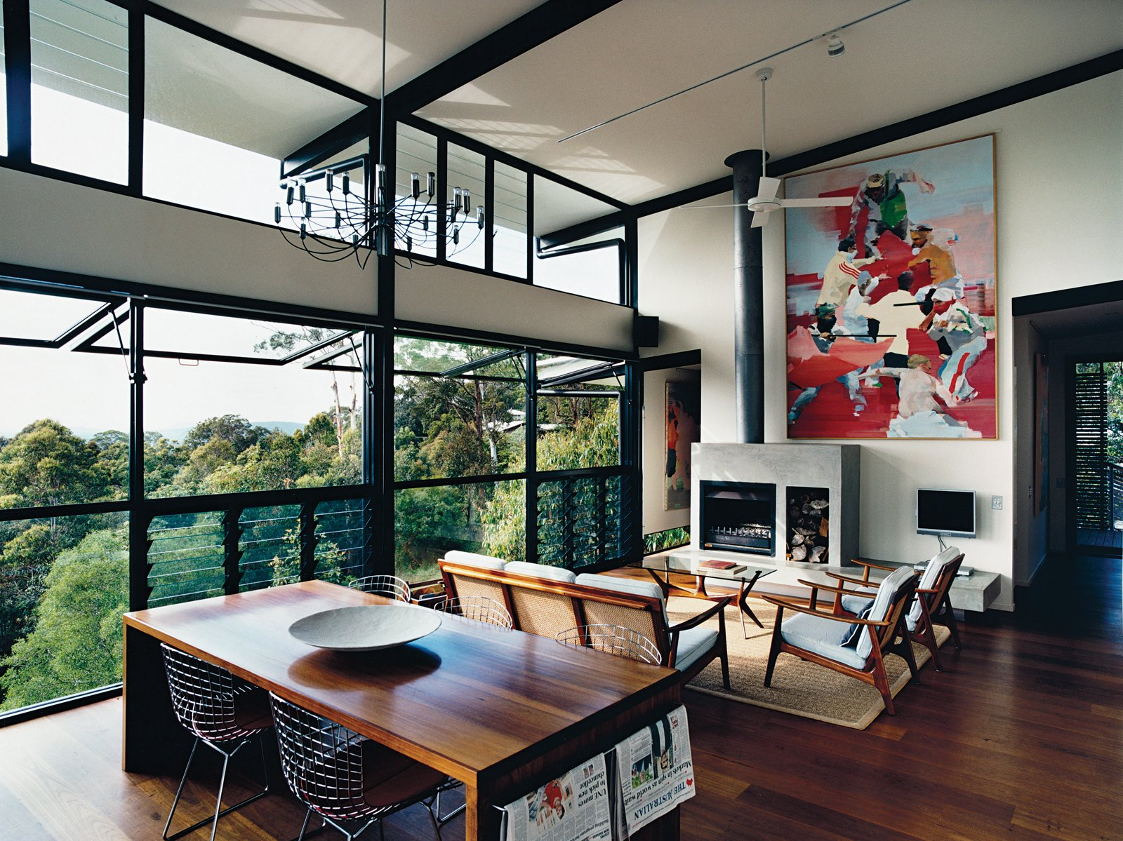 The open-plan living room was inspired by the couple's previous residence, a London loft. The paintings are by Dunlop. The louvered floor-to-ceiling windows, ceiling fan, and sliding deck doors usher in sea breezes and encourage good air circulation. Tagged: Living Room, Medium Hardwood Floor, Standard Layout Fireplace, Chair, Wood Burning Fireplace, Pendant Lighting, and Sofa.  Photo 4 of 12 in Hillside Family Home in Australia