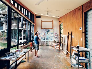 Hillside Family Home in Australia - Photo 6 of 12 - In his detached painting studio, Dunlop considers a work in progress. The building is oriented east-west to avoid direct sunlight, and the long, narrow shape enables the artist to get some distance from his paintings as he works. An oversize front door and angled ceiling accommodate extra-large canvases; the plywood walls and floor can <br><br>ably endure a beating, or, as is more likely, stray splashes of paint.
