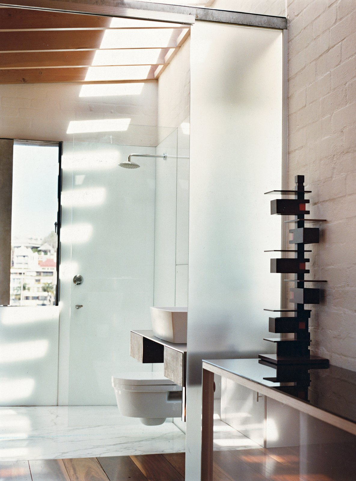 The sun cuts down into the upstairs bathroom through skylights, casting rhythmic shadows of roof beams onto the floor and walls. The bathroom includes a cantilevered toilet by Catalano.