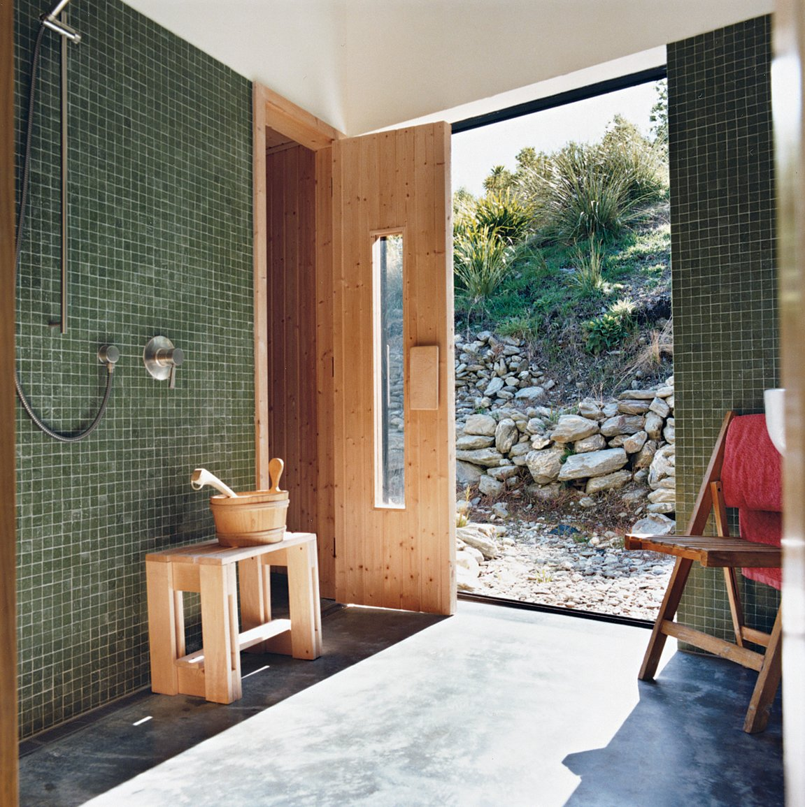 Queenstown gets cold in winter, hence the installation of a sauna. Outside, the landscaping was kept deliberately casual, with rock walls and gravel paths. Tagged: Bath Room, Concrete Floor, Glass Tile Wall, and Open Shower.  Photo 6 of 12 in Nature Nurtured